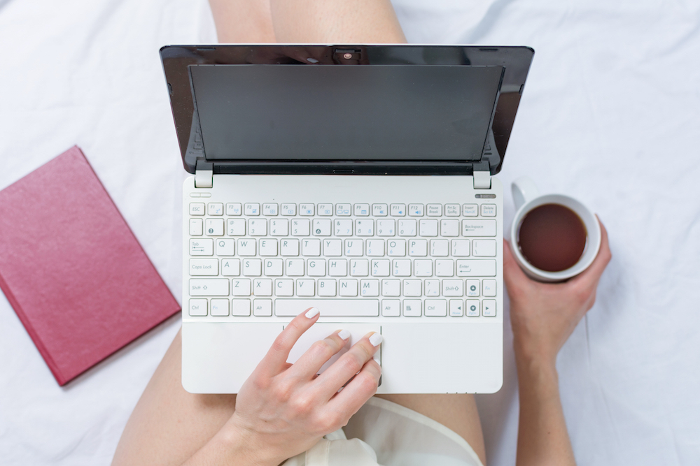 Woman working on a notebook while in bed