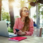 Young creative woman work on laptop while having breakfast on terrace, flare sun